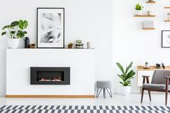 Poster and plant on white board with fireplace in cosy living room interior with armchair. Real photo. Poster and plant on white wall with fireplace in cozy stock image