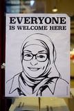 Poster representing a Muslim woman with a hijab veil saying Everyone is Welcome Here. NEW YORK CITY, NY -Poster on a shop window representing a smiling Muslim Stock Image