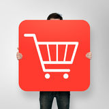 Poster with shopping cart icon. Man holding poster with shopping cart icon Stock Photos