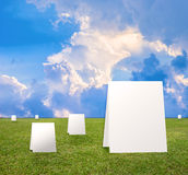 Poster standing on Green field under blue clouds sky. Royalty Free Stock Photography