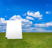Poster standing on Green field under blue clouds sky. Stock Photo