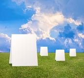 Poster standing on Green field under blue clouds sky. Royalty Free Stock Photo