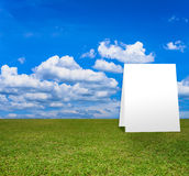 Poster standing on Green field under blue clouds sky. Royalty Free Stock Images