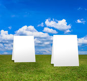 Poster standing on Green field under blue clouds sky. Royalty Free Stock Photos