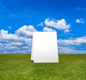 Poster standing on Green field under blue clouds sky. Stock Photography