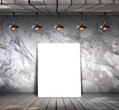 Poster standing on wood floor with Grungy concrete wall Stock Photo