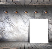 Poster standing on wood floor with Grungy concrete wall Royalty Free Stock Photo