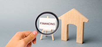 A poster with the word Financing and a wooden house. Attracting investment in housing and architectural buildings. Risk assessment. Infrastructure development royalty free stock photos