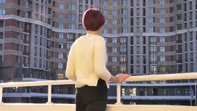Posterior-retrato de la situación rosado-cabelluda hermosa de la muchacha cerca de cercar con barandilla y de la observación en l metrajes
