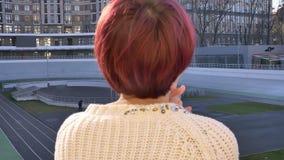 Posterior-retrato del primer de la situación rosado-cabelluda hermosa de la muchacha cerca de cercar con barandilla y cuidadosame metrajes