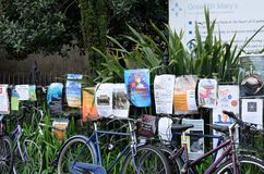Posters and Bikes by railings in Cambridge Uk. Cambridge England, United Kingdom -May 20, 2016: Posters and Bikes by railings in Cambridge Uk Royalty Free Stock Photography
