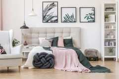 Posters in cozy bedroom interior. Pastel bedding on bed with grey bedhead in cozy bedroom interior with armchair and posters royalty free stock photography