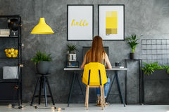 Posters mock-up in study space. Girl sitting at her desk in posters mock-up interior with study space and modern yellow chair Royalty Free Stock Photos