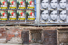 Posters and wall. Damaged wall and advertisement posters on billboard in Poznan, Poland Royalty Free Stock Images