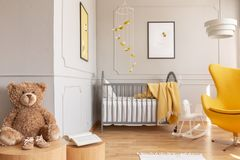 Posters on the walls of chic baby bedroom with grey and yellow design