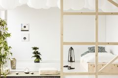 Posters on white wall above bonsai in bedroom interior with lantern. Next to wooden bed. Real photo stock photos