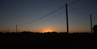 Postes con los alambres en la puesta del sol Fotos de archivo