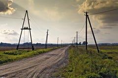 Postes de la electricidad a lo largo del camino. Fotos de archivo