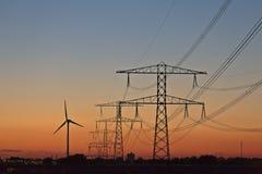 Postes de la energía eléctrica y turbina de viento Foto de archivo libre de regalías
