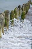 Postes de madera en el mar imagenes de archivo