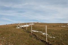 Postes de madera y alambre de púas de la cerca que marcan la línea de propiedad de una pradera con la hierba secada y de remiendo fotos de archivo libres de regalías