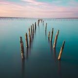 Postes en el agua - en las nubes y el océano de la puesta del sol Imagen de archivo libre de regalías