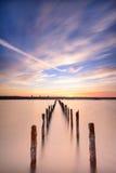 Postes en el agua - en las nubes y el océano de la puesta del sol Foto de archivo