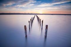 Postes en el agua - en las nubes y el océano de la puesta del sol Fotografía de archivo