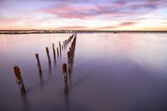 Postes en el agua - en las nubes y el océano de la puesta del sol Imagenes de archivo