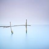 Postes y agua suave en paisaje de niebla. Exposición larga. Fotografía de archivo