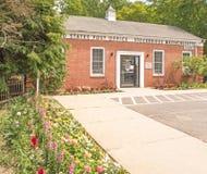 Postgebäudeeingang und -Bürgersteig Vereinigter Staaten mit Blumengarten stockbild