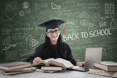Postgraduate studying in class. Young female bachelor studying with laptop and books in class Stock Photo