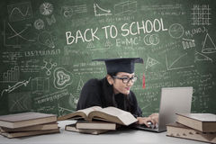 Postgraduate studying in class 3. Young female bachelor studying with laptop and books in class Stock Photography