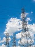 Posti de alto voltaje de la electricidad con la nube y el cielo azul imagenes de archivo
