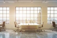 Posti di lavoro in un ufficio dello spazio aperto del sottotetto di tramonto Le Tabelle sono fornite di computer Immagini Stock
