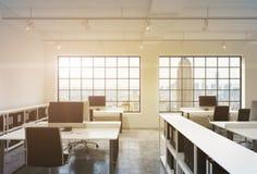 Posti di lavoro in un ufficio dello spazio aperto del sottotetto di tramonto Le Tabelle sono fornite di computer; scaffali di lib Fotografia Stock