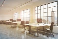 Posti di lavoro in un ufficio dello spazio aperto del sottotetto di tramonto Le Tabelle sono fornite di computer; scaffali di lib Immagine Stock