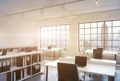 Posti di lavoro in un ufficio moderno luminoso dello spazio aperto del sottotetto Tabelle fornite di computer portatili; gli scaf Immagini Stock