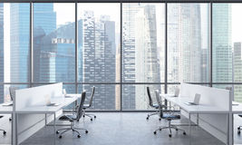 Posti di lavoro in un ufficio moderno luminoso dello spazio aperto Tavole bianche fornite dei computer portatili moderni e delle  Fotografia Stock