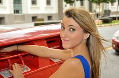 Posting a letter. Young lady posting a letter at a Brisbane city post box Royalty Free Stock Photos