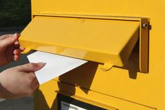 Posting a letter. Into mailbox Stock Photo