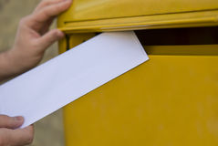 Posting a Letter. Man's hands posting a letter in a yellow post box Stock Photography