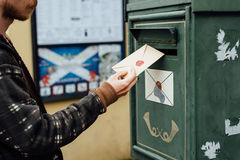 Posting letter to old postbox on street Stock Image