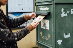 Posting letter to old postbox on street Royalty Free Stock Images