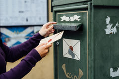 Posting letter to old postbox on street Royalty Free Stock Image