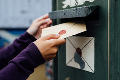 Posting letter to old postbox on street Royalty Free Stock Photography