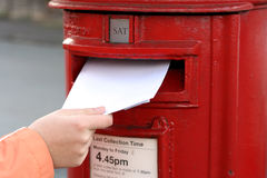 Posting letter to red british postbox Royalty Free Stock Images