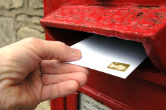 Posting a letter in the UK. Posting a letter in an old red postbox mounted in a wall in the UK Stock Photography