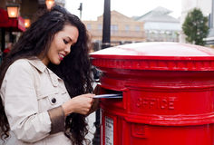 Posting letters. A young woman posting letters Stock Image