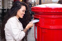 Posting letters. A young woman posting letters Royalty Free Stock Images